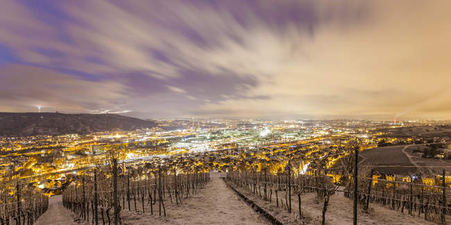 Hill with snow and plants under clouds at night — Stock Photo