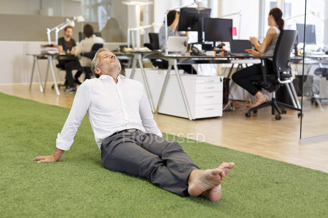 Relaxed businessman sitting on carpet in office — Stock Photo