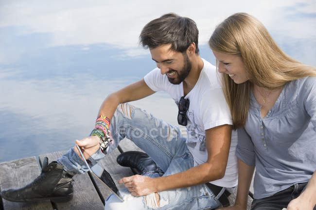 Smiling young couple sitting on jetty at a lake with tablet — Stock Photo