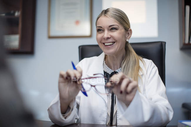 Female optometrist talking to patient, holding spectacles in medical clinic — Stock Photo