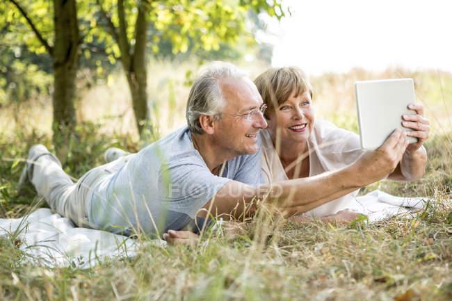 Старшая пара лежит на одеяле в природе с цифровой планшет — стоковое фото