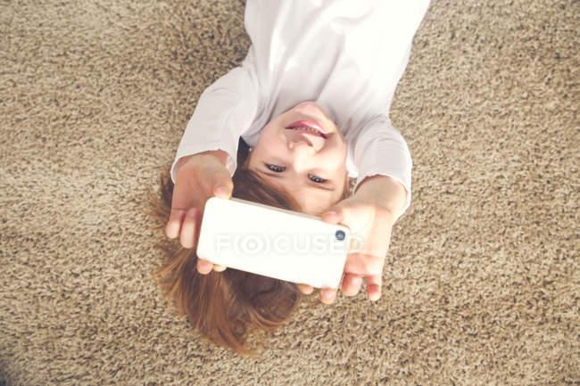 Портрет посміхаючись дівчинка, лежачи на килимі беручи selfie зі смартфона — стокове фото