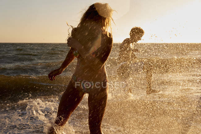 Playful couple in the sea at sunset — Stock Photo