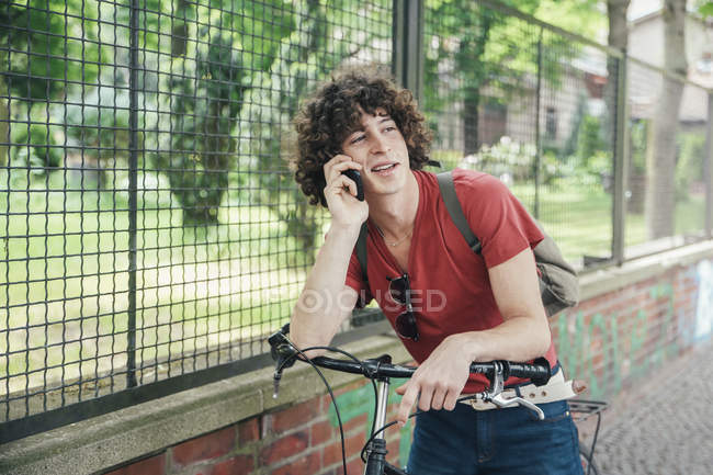 Young man standing with bicycle on the phone — Stock Photo