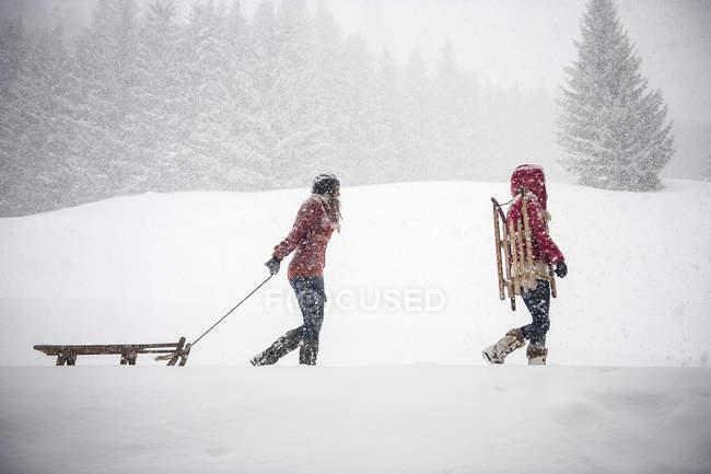 Dos mujeres jóvenes con trineos en nieve pesada - foto de stock