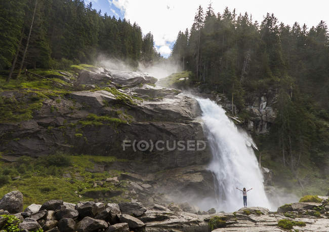 Woman with raising arms standing by Krimml Waterfalls in Salzburg, Austria — Stock Photo