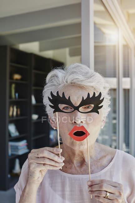 Seniorin versteckt sich hinter Papiermasken — Stockfoto