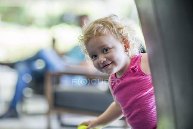 Дівчинку посміхаючись від кута будинку — стокове фото