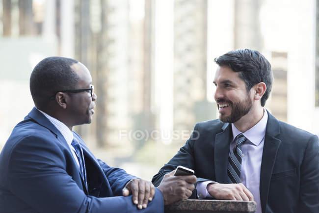 Deux hommes d'affaires souriants parlent à l'extérieur — Photo de stock