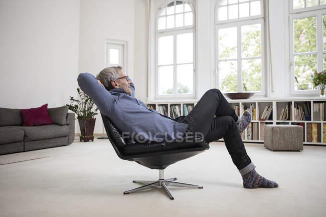 Entspannte reifer Mann sitzt im Stuhl moderne zuhause — Stockfoto