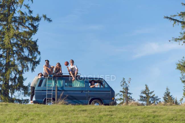 Группа друзей, сидящих на крыше фургона в природе — стоковое фото