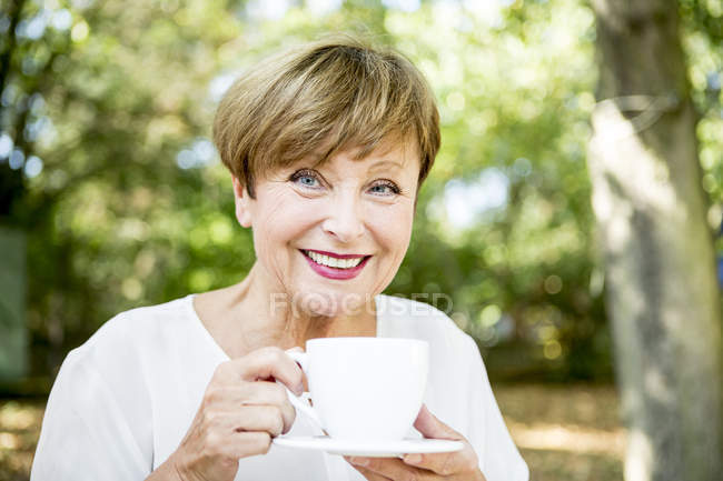 Portrait of smiling senior woman holding cup of coffee outdoors — Stock Photo