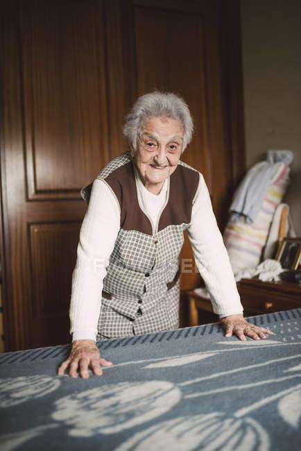 Smiling Senior woman making bed — Stock Photo