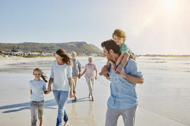 Retrato de tres generaciones de familia paseando en la playa - foto de stock