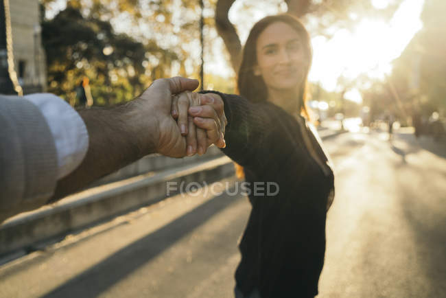 Woman holding hands with boyfriend at sunset — Stock Photo