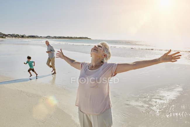 Portrait von senior Frau mit ausgestreckten Armen am Strand — Stockfoto