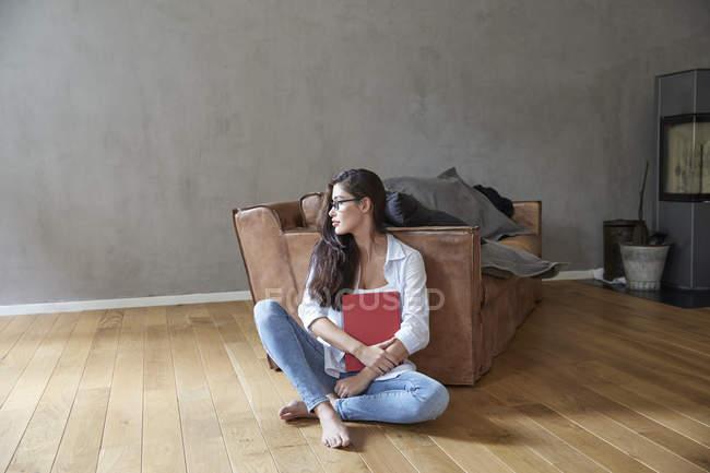 Jovem mulher sentada com livro no chão de madeira em casa — Fotografia de Stock