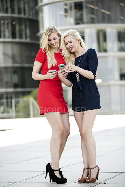 Two fashionable women looking at their smartphones — Stock Photo