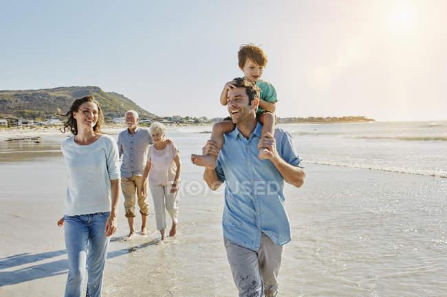 Retrato de sonriente familia tres generaciones paseando en la playa - foto de stock