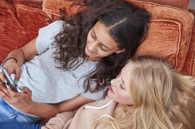 Duas meninas deitadas no sofá e usando smartphone — Fotografia de Stock