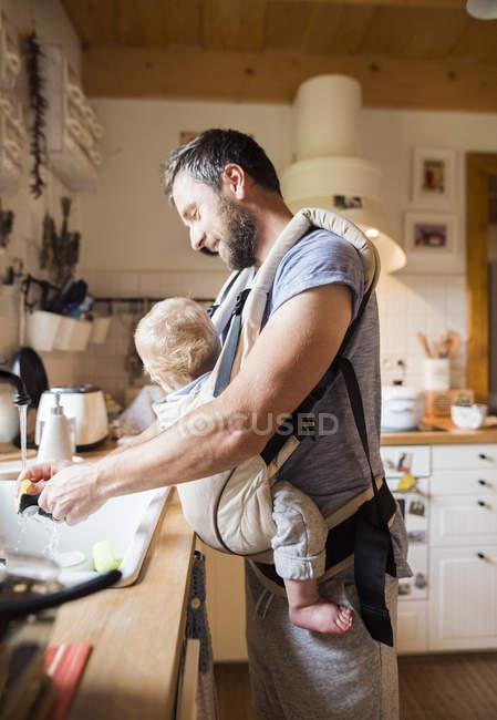 Père heureux avec bébé dans le porte-bébé faisant la vaisselle — Photo de stock