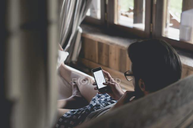Retrato cortado de homem jovem usando smartphone na cama — Fotografia de Stock