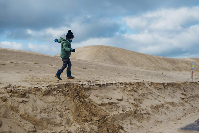 Denmark, North Jutland, boy running in wandering dunes at lighthouse Rubjerg Knude — Stock Photo