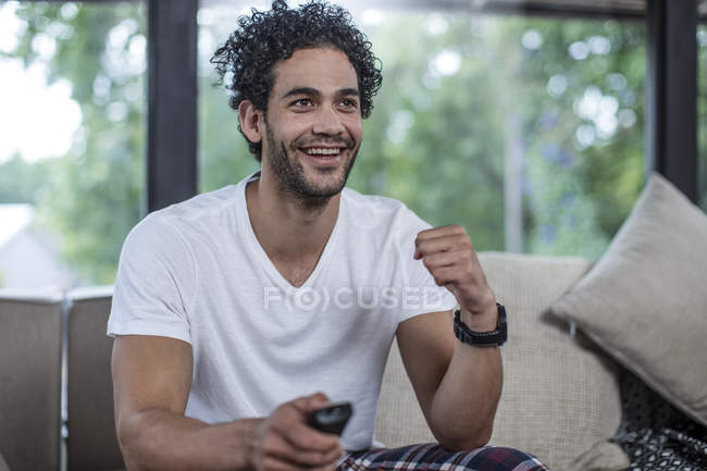 Happy young man sitting on couch watching tv — Stock Photo