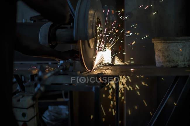 Gros plan du mécanicien à l'aide d'une meuleuse de banc en atelier — Photo de stock