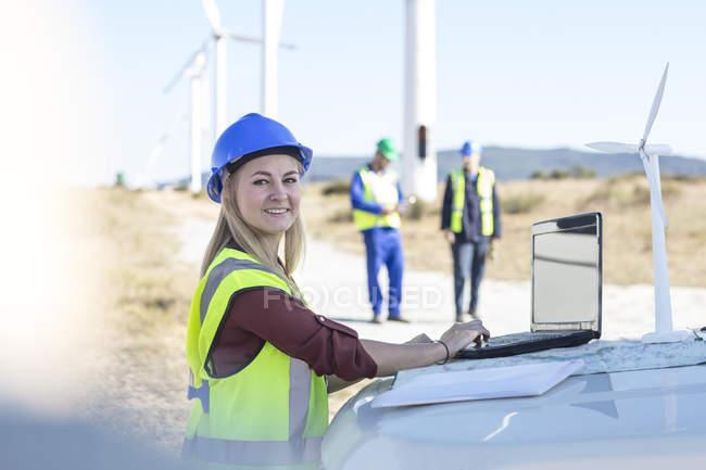 Ingénieur femme travaillant sur un parc éolien, utilisant un ordinateur portable — Photo de stock
