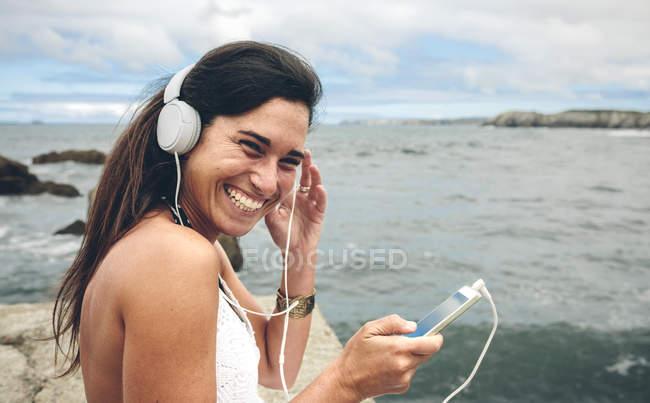 Femme riante écoutant de la musique avec écouteurs en face de la mer — Photo de stock