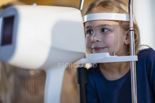 Girl doing eye test at the optometrist in medical clinic — Stock Photo