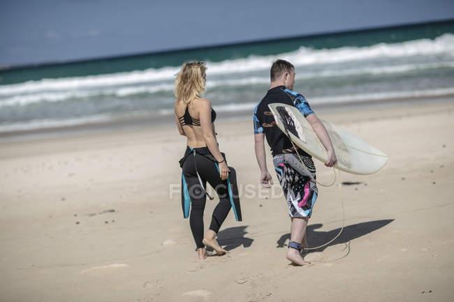 Adolescent avec le syndrome de down et de la femme avec planche de surf sur la plage — Photo de stock