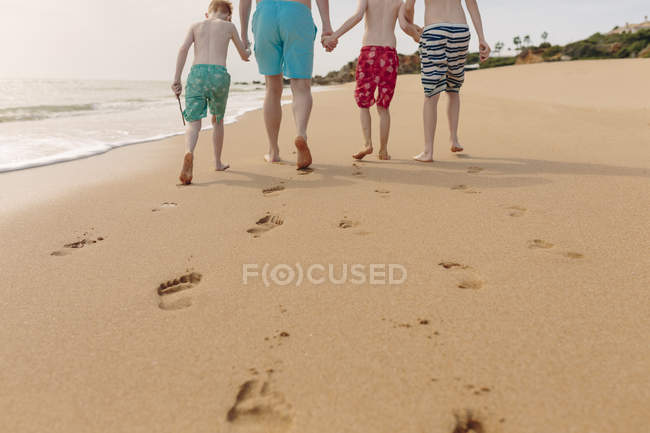 Father and sons walking on the beach at summer vacation — Stock Photo