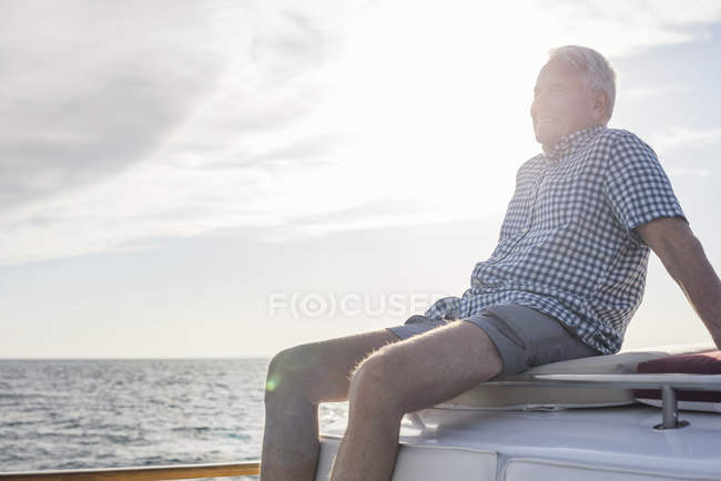 Smiling senior man on boat trip looking at view — Stock Photo