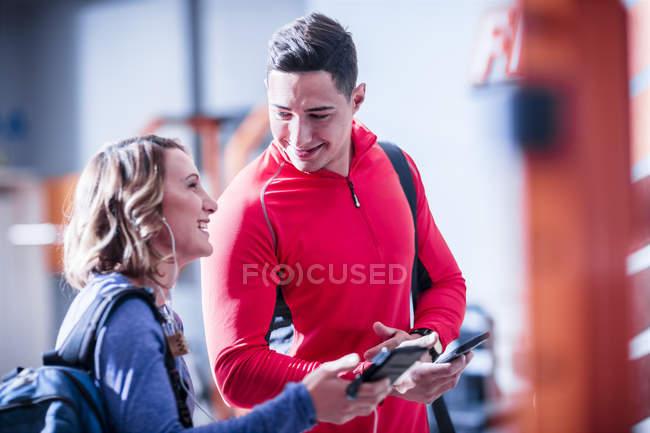 Jovem homem e mulher com telefones celulares e fones de ouvido no ginásio — Fotografia de Stock