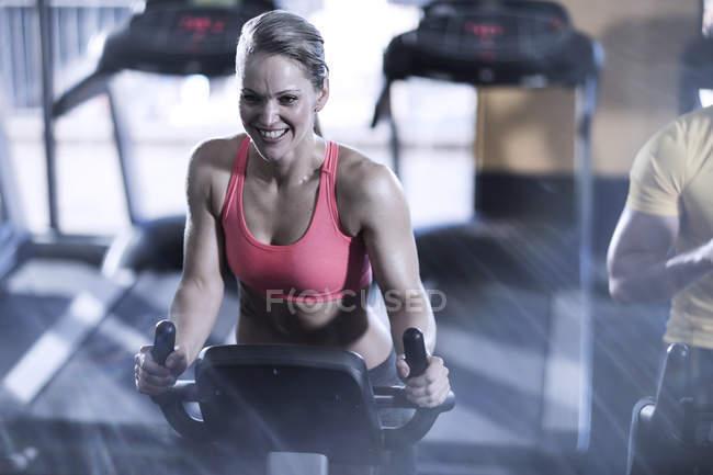 Lächelnde Frau auf Spinning-Bike im Fitness-Studio trainieren — Stockfoto