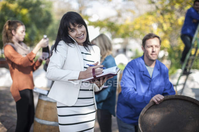 Wine saleswoman talking on phone with clients and wine worker on background — Stock Photo