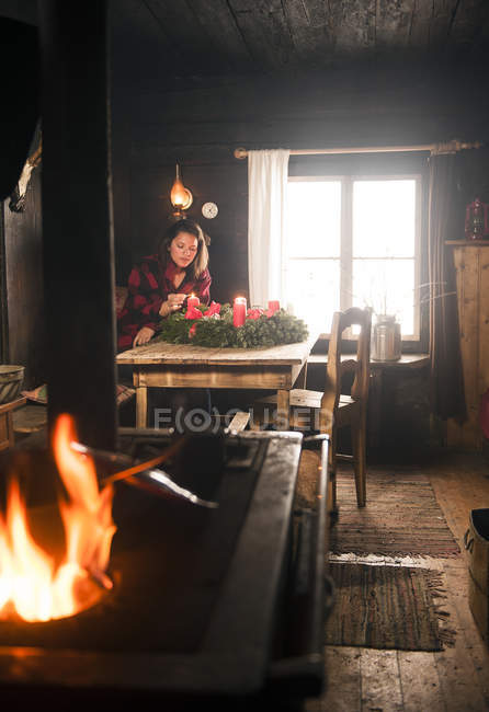 Woman in a wooden hut lighting candle on Advent wreath — Stock Photo