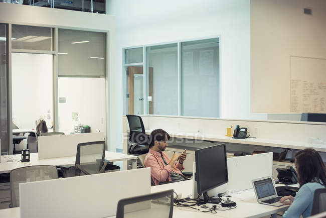 Люди, работающие в офисе, используя мобильные устройства — стоковое фото