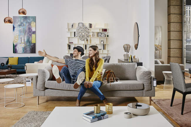 Portrait of couple sitting on sofa in furniture store — Stock Photo