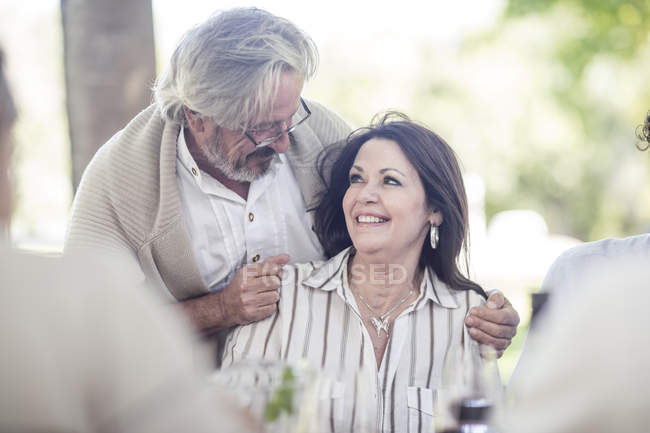 Elderly man hugging elderly woman sitting at outside table — Stock Photo