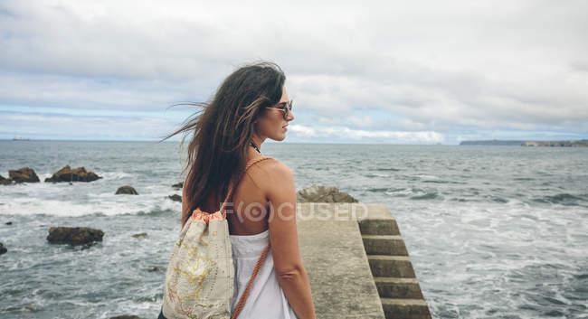 Mujer con mochila de pie en el muelle y mirar a la distancia - foto de stock
