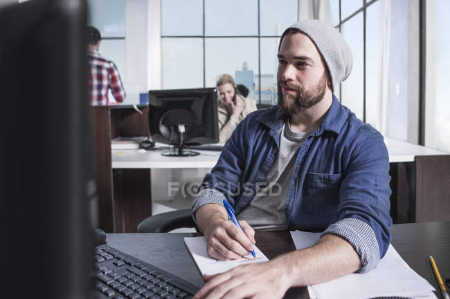 Casual male on keyboard with computer at office desk — Stock Photo