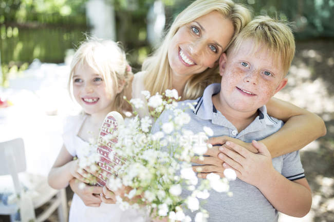 Smiling mother with Mothers Day gifts hugging children — Stock Photo