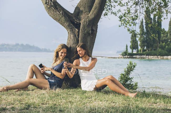 Itália, Lago de Garda, duas mulheres jovens, encostado a uma árvore usando telefones celulares — Fotografia de Stock
