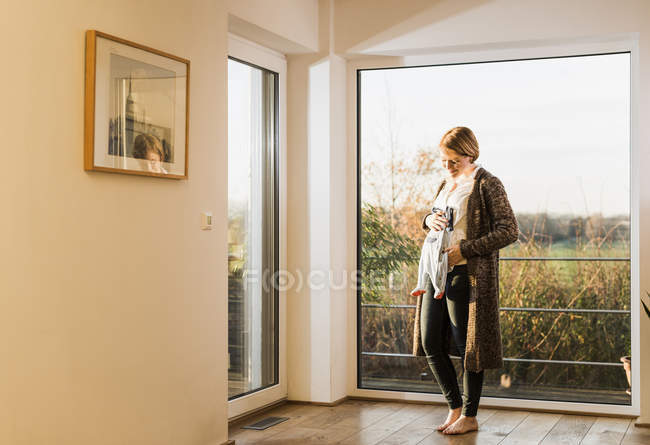 Pregnant woman standing at window and holding baby clothes — Stock Photo