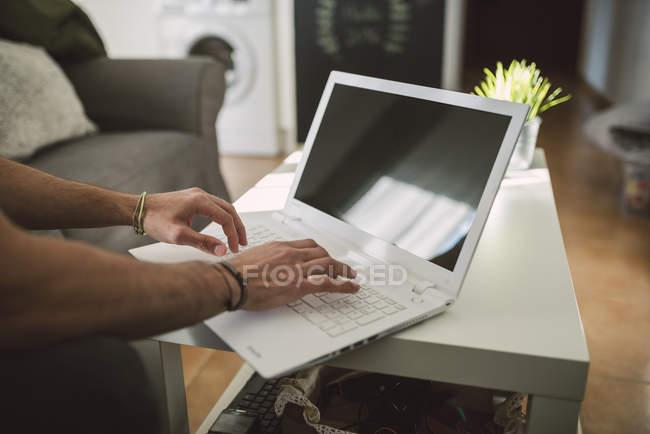 Vista ritagliata di un uomo che utilizza un computer portatile a casa — Foto stock