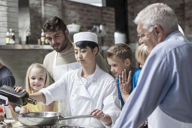 Chef with group of learners adding oil to pan in cooking class — Stock Photo