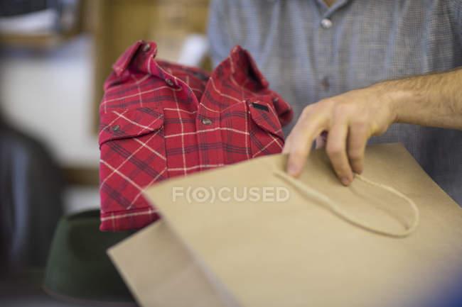 Homme mettre une nouvelle chemise dans le panier — Photo de stock